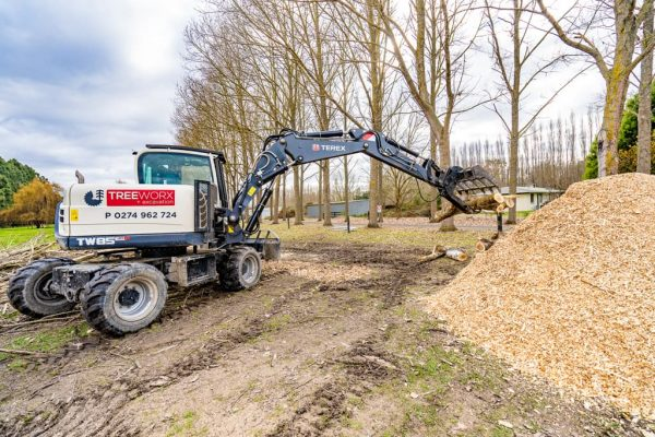 Using an excavator to mulch logs in North Canterbury